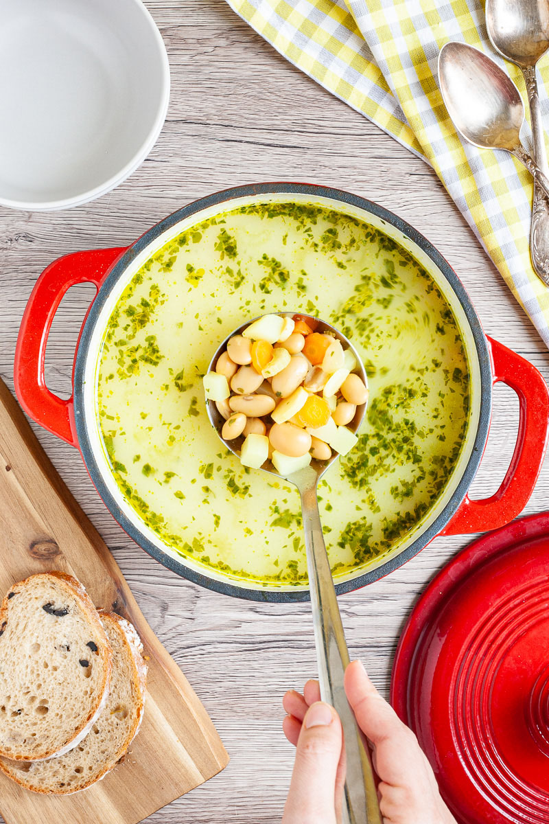 Yellow soup with chopped herbs is served in a large red dutch oven. A laddle is full of white beans, diced potatoes and carrot slices as it takes one serving.