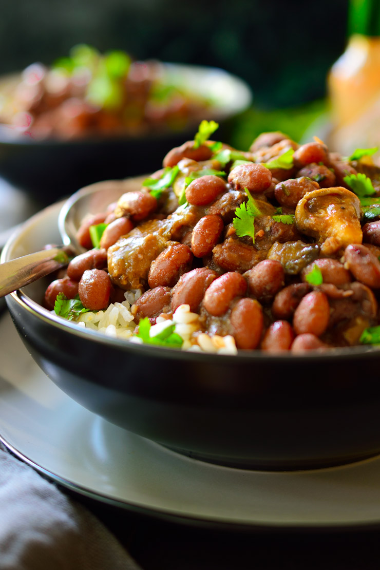 Black bowl with rice topped with beans and mushrooms shreds in a dark brown sauce.