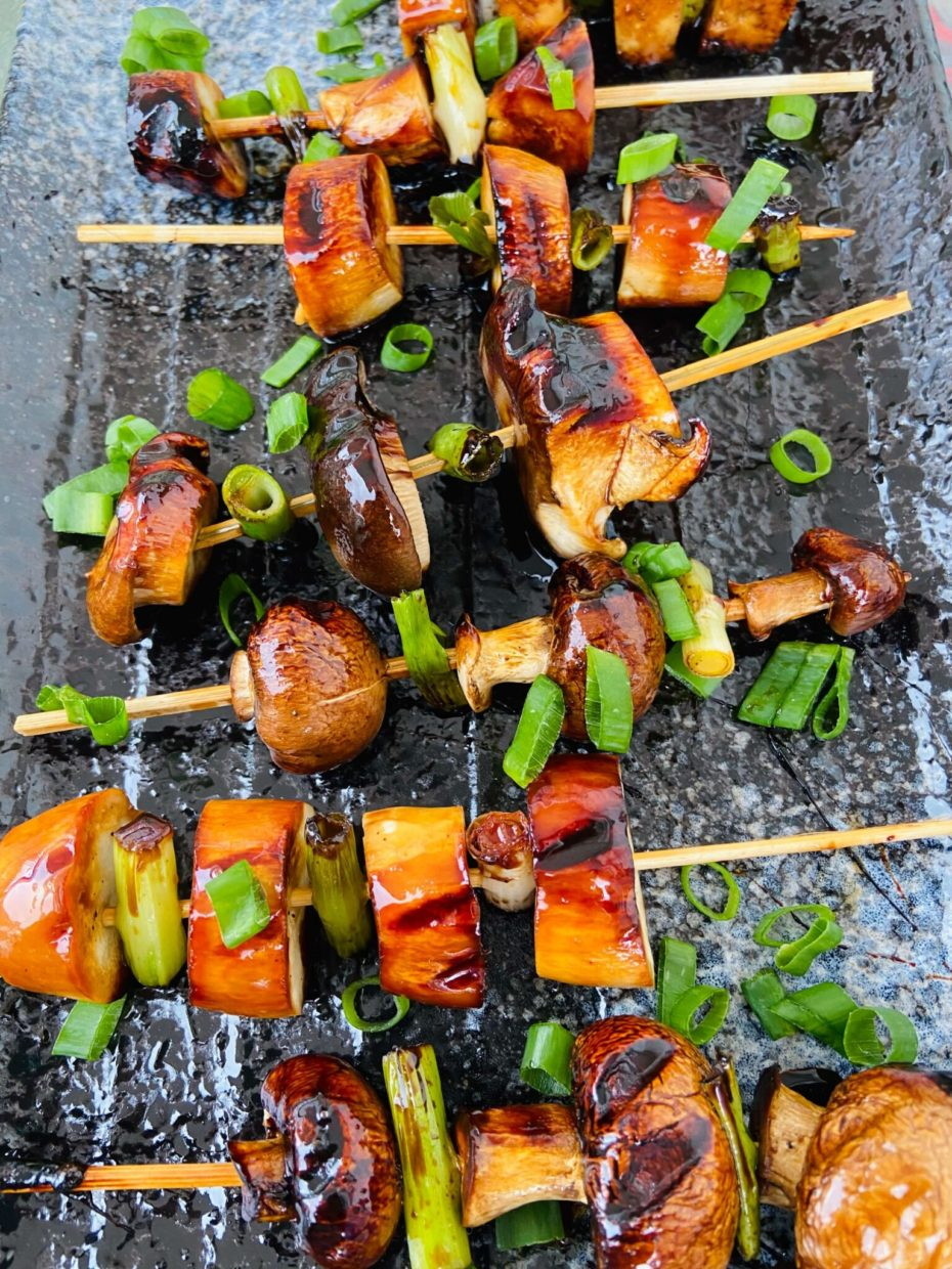 Wooden skewers with mushroom slices grilled to dark brown almost black on the edges. They are sprinkled with green onion rings