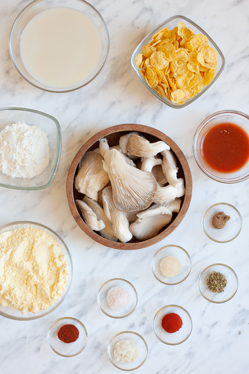 The ingredients to make vegan chicken wings are placed in several glass bowls: milk, flour, corn flakes, oyster mushrooms, hot sauce, different spices and herbs