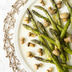 White round plate from above with green asparagus scattered around in between button mushrooms. It is sprinkled with yellow powder.