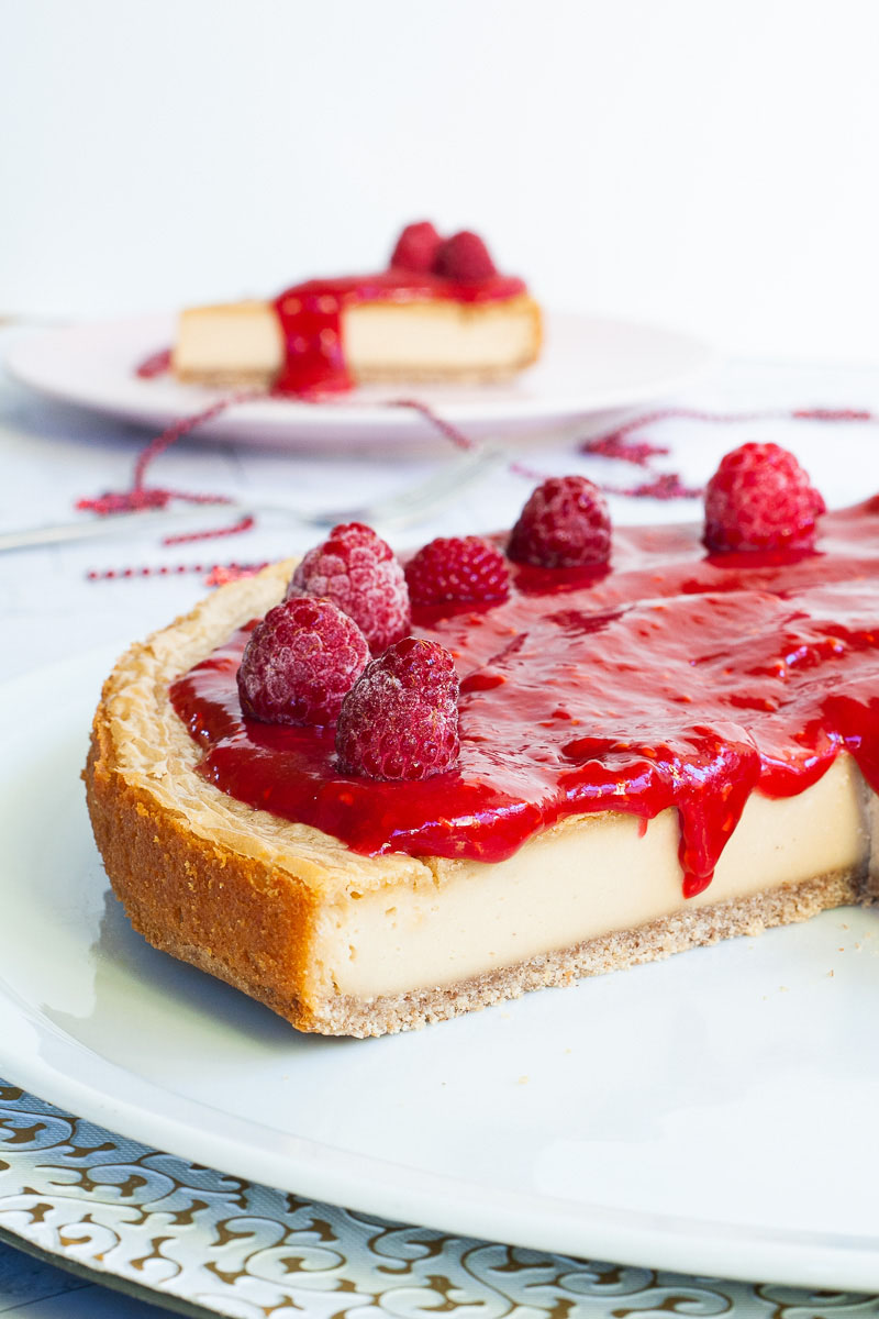 A light yellow cheesecake with vibrant red sauce and raspberries on top is placed on a large round white plate. One slice on a pink plate is behind it.