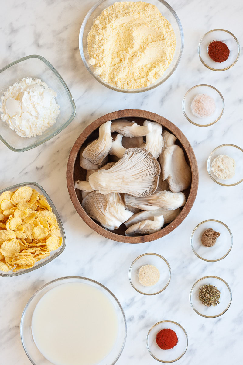 Lots of bowls with the ingredients to make vegan fried chicken: oyster mushrooms, different spices, yellow flour, starch, milk, corn flakes