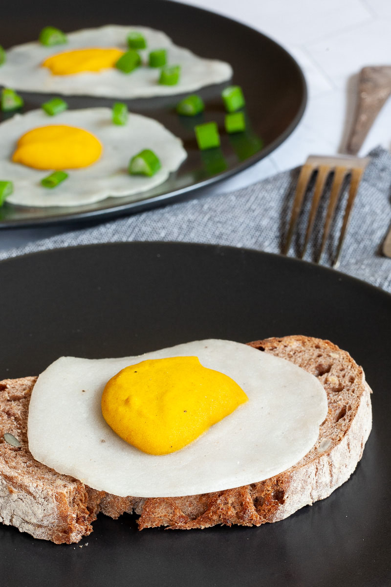 3 fried egg lookalike with white and yolk part on top a crusty brown bread served on a black plate. Fork and knife on the side. There is another black plate in the back with two more fried eggs
