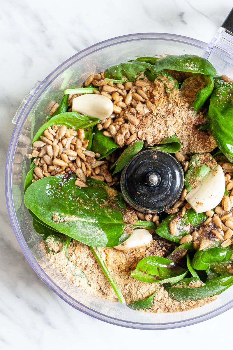 Food processor from above with sunflower seeds, fresh spinach and basil leaves, garlic clove and yellow powder to make pesto.