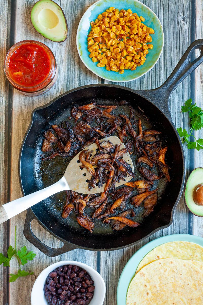 Crispy dark brown oyster mushroom shreds in a black cast-iron skillet. A spatula is holding up a handful. One small bowl with black beans, one with red sauce and one blue plate with corn
