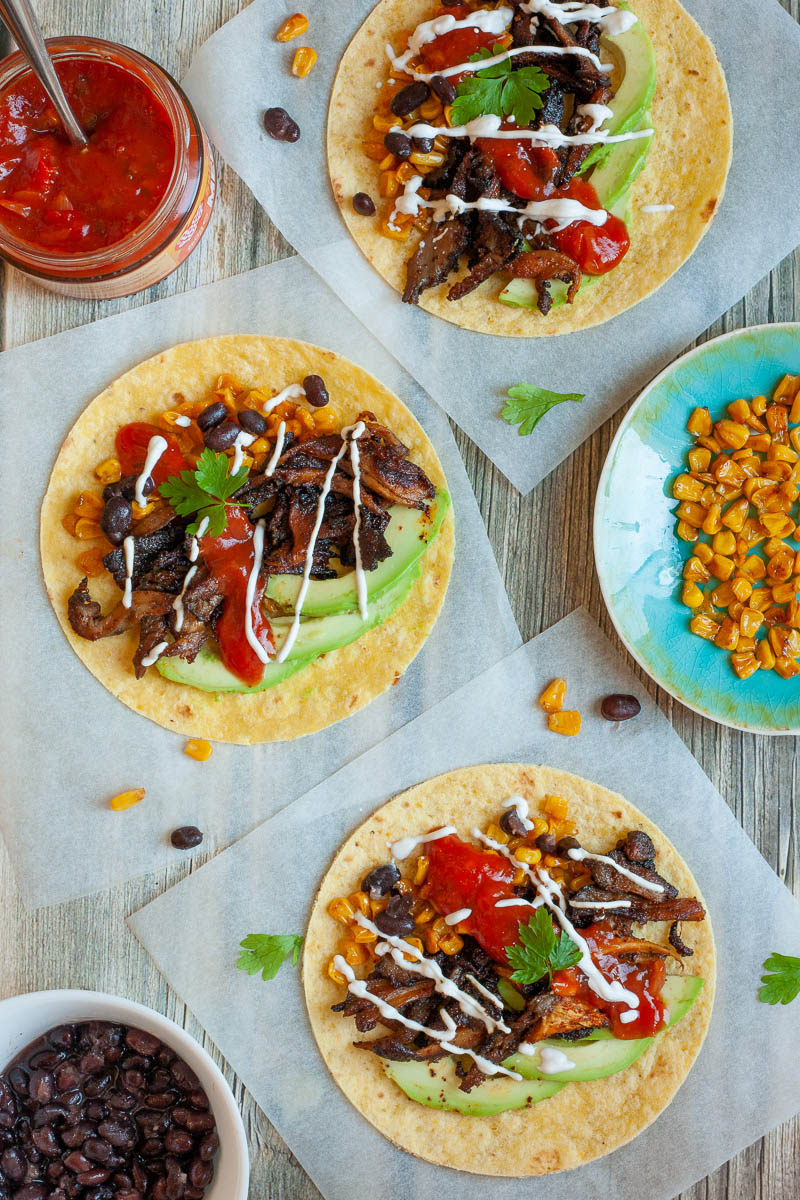 3 small tortillas on parchment paper filled with mushroom shreds, corn, avocado slices, black beans drizzled with red and white sauce. One small bowl with black beans, one with red sauce and one blue plate with corn