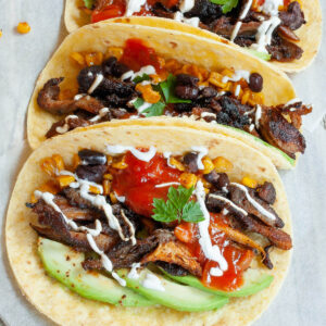 3 small tortillas folded in half on parchment paper filled with mushroom shreds, corn, avocado slices, black beans drizzled with red and white sauce.