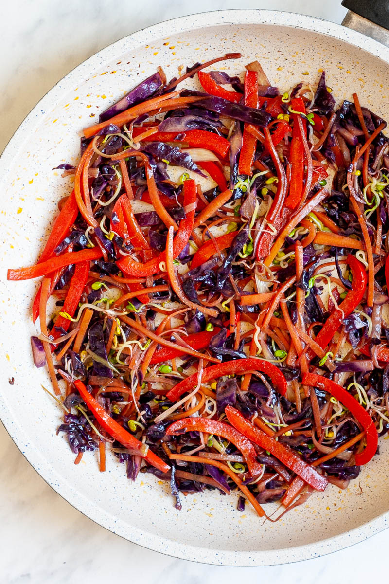 A white frying pan with shredded veggies like carrots, purple cabbage, bell pepper, bean sprouts.