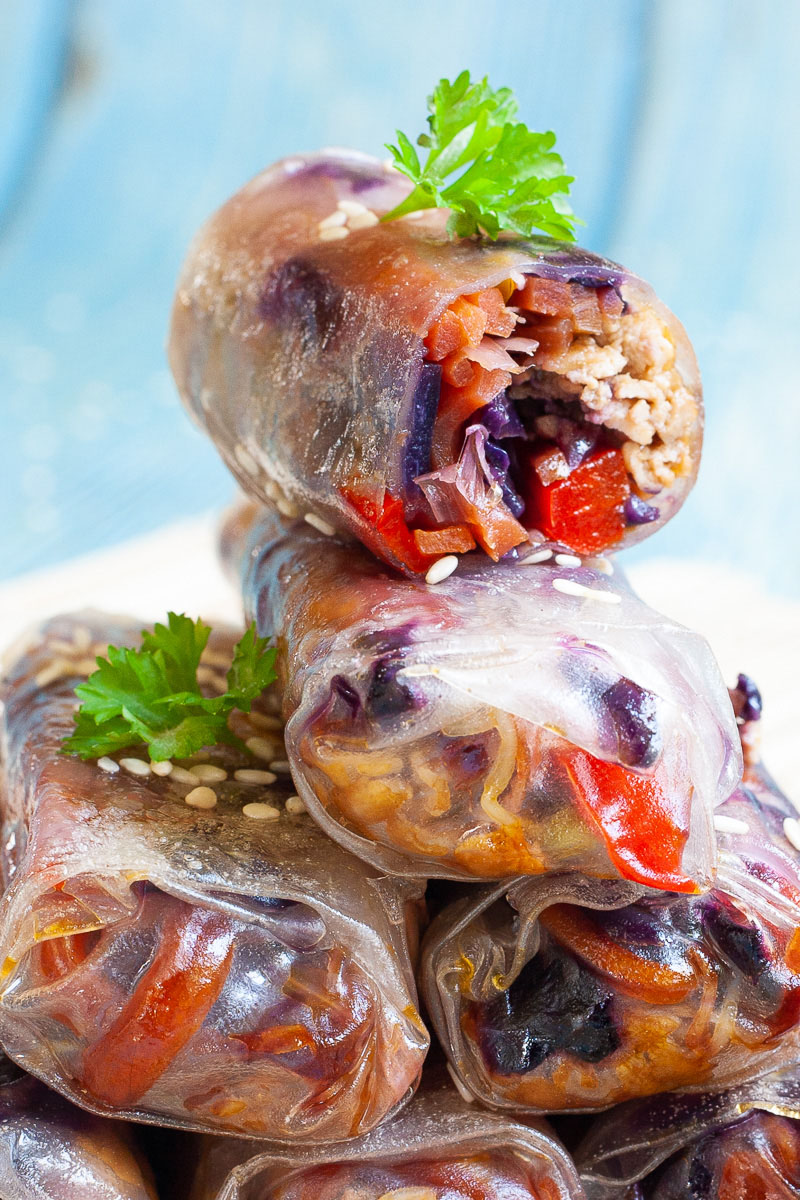 Lots of spring rolls placed on top of each other like a pyramid.The top one is cut in half so you can see inside the purple cabbage bits and some carrot and bell pepper pieces.