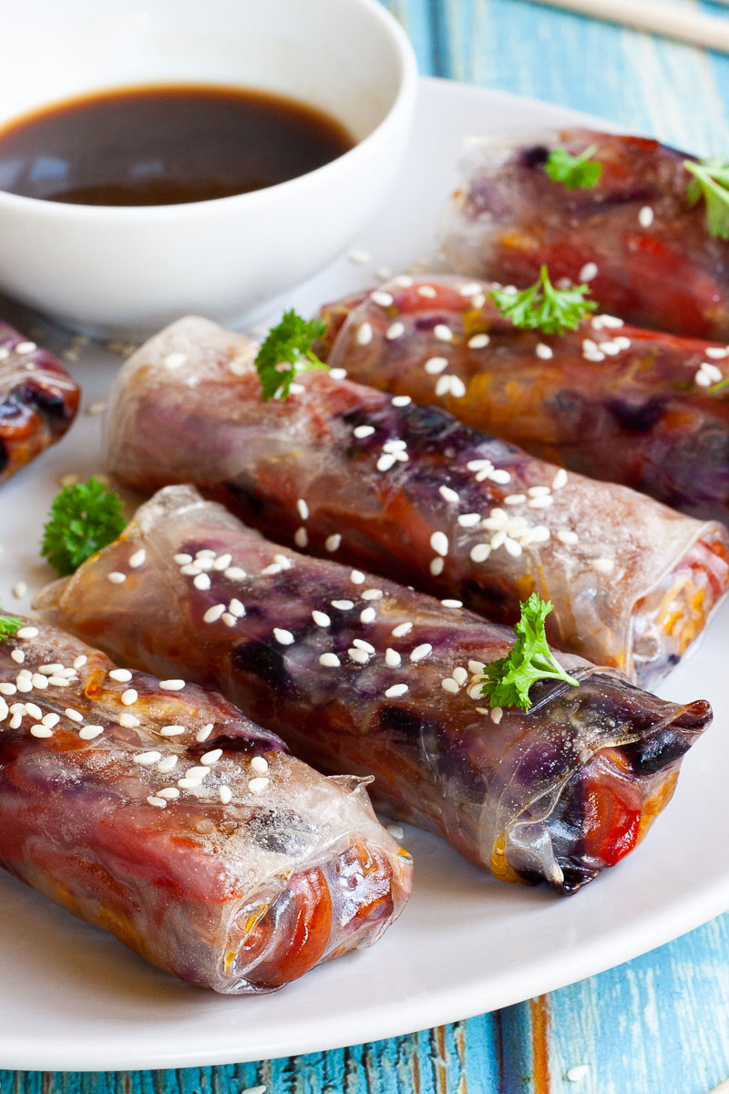 A couple of spring rolls are arranged on a white plate sprinkled with sesame seeds and chopped parsely. They are transparent so you can see red, orange and purple veggie pieces.