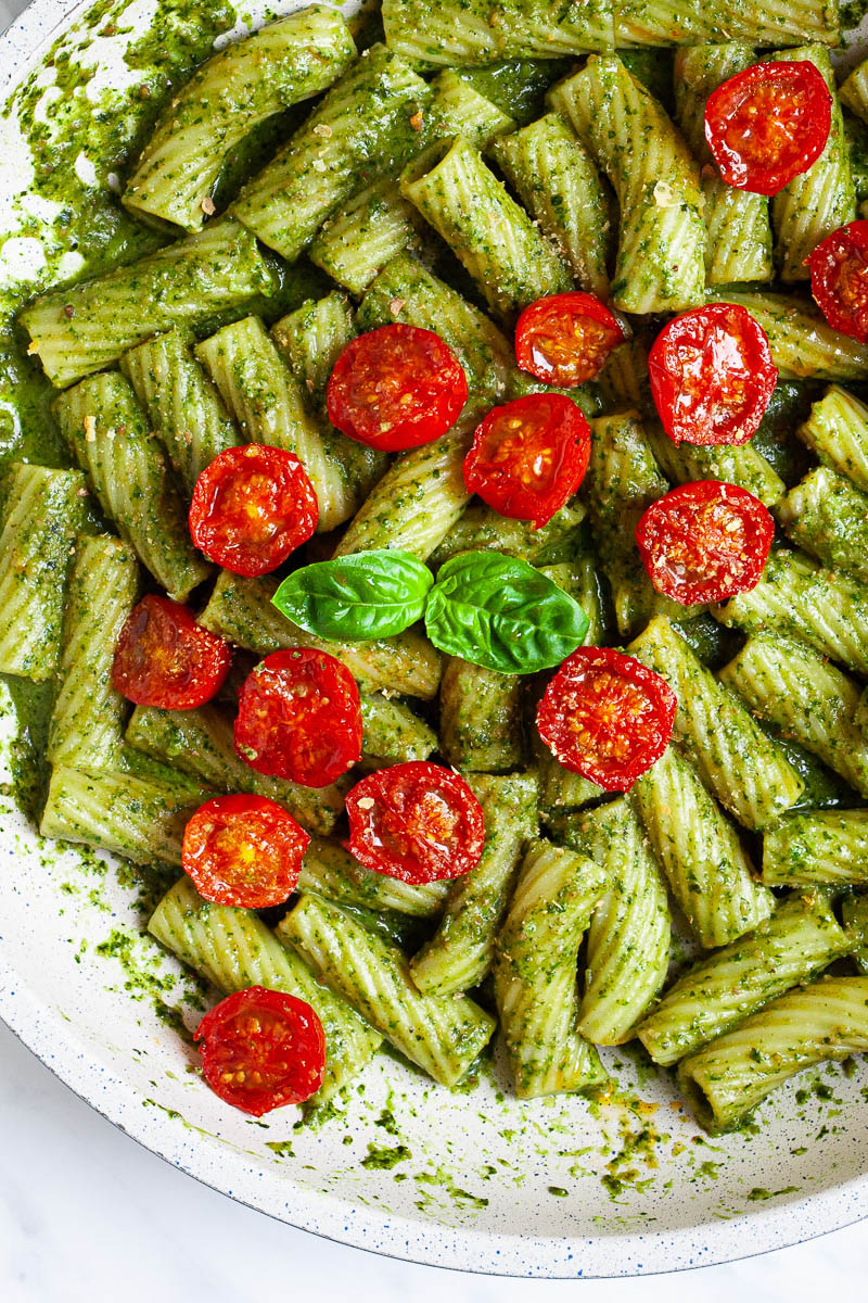 White frying pan with tortiglioni pasta covered in green paste, wilted half cherry tomatoes are on top scattered.