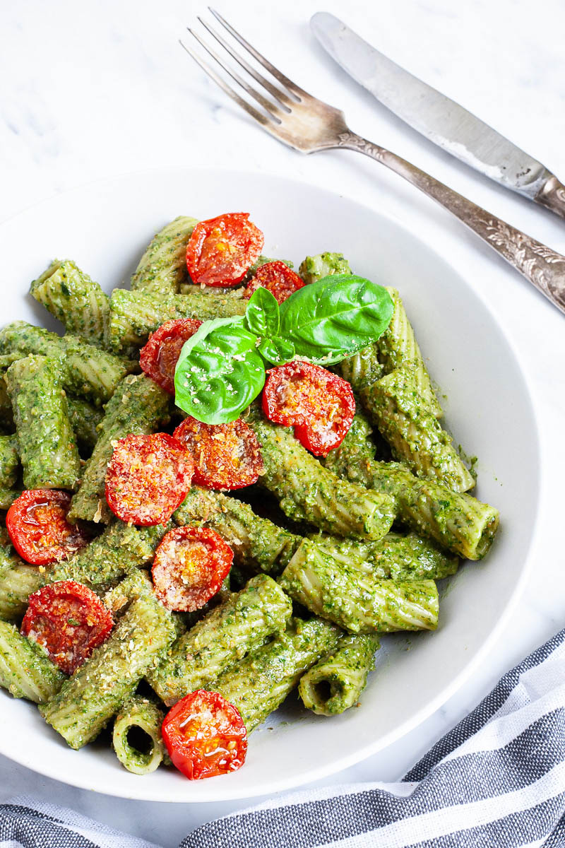 White bowl with tortiglioni pasta covered in green pesto topped with cherry tomato halves and sprinkled with yellow flakes.