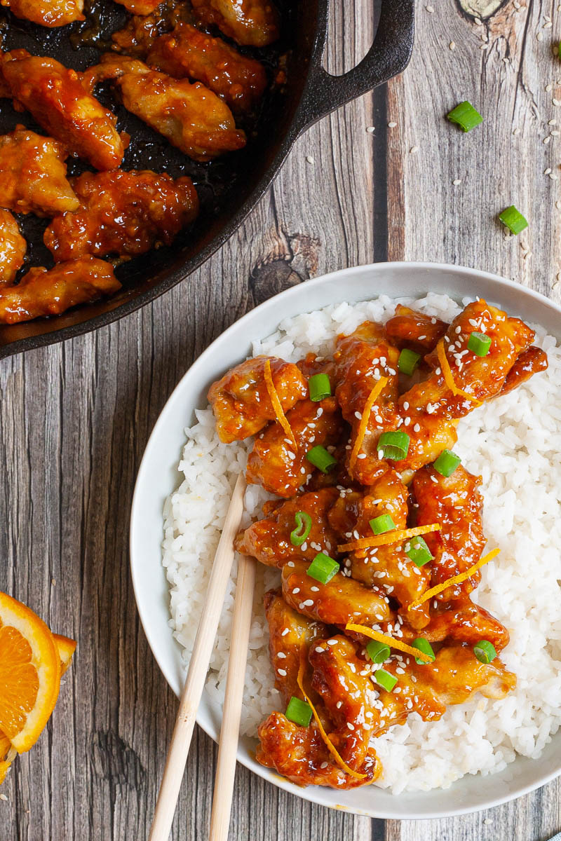 A large white bowl from above with white rice and sticky brown battered strips on top sprinkled with sesame seeds, orange peels and chopped spring onion. A black cast-iron skillet with the remaining strips is in the corner.