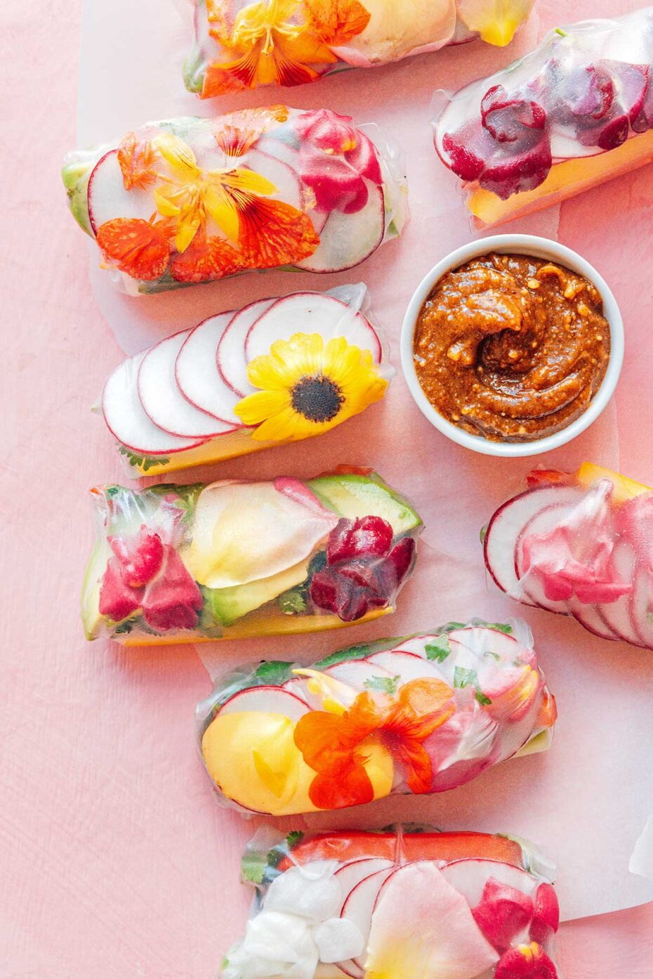 Colorful rice paper rolls with flowers on a pink surface