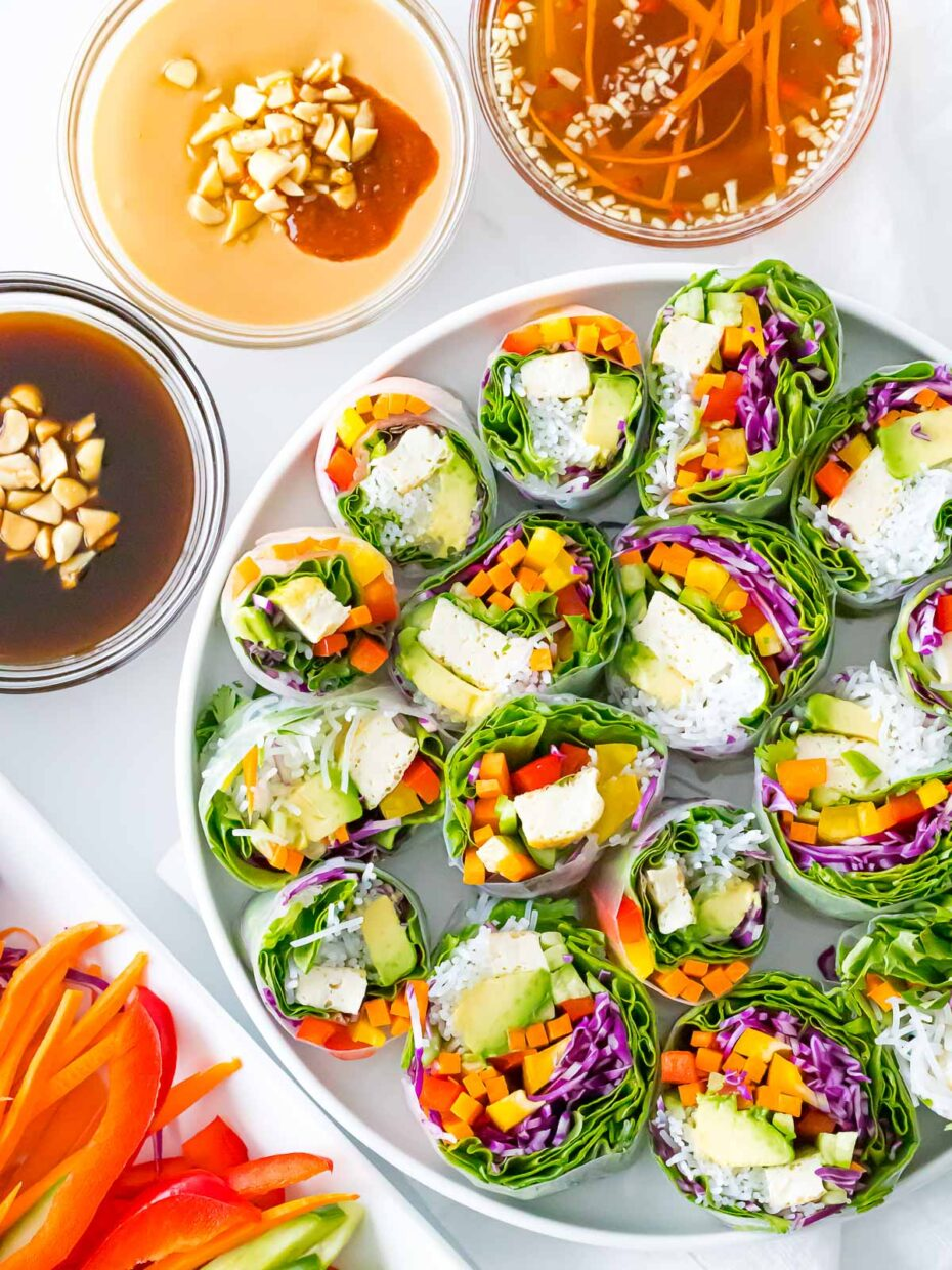 Large white plate with lots of rolls cut in half so you can see the colorful filling of green, red, white, yellow. 3 small bowls of dipping sauce are around it.