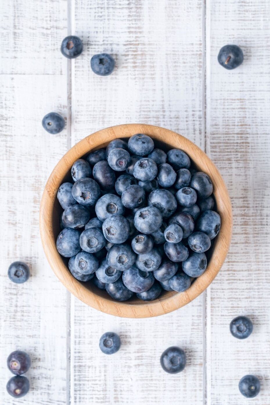 Brown wooden bowl in the middle of a white washed wooden board full of blueberries. Some are scattered around