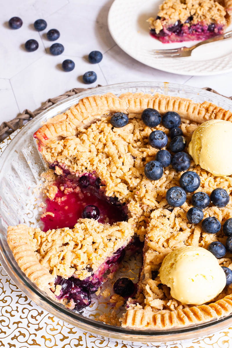A whole blueberry pie from above with fresh blueberries on top as decoration, crumble topping and 2 scoops of yellow ice cream. 2 slices are missing. A plate with one slice is in the background. Fresh blueberries are scattered around.