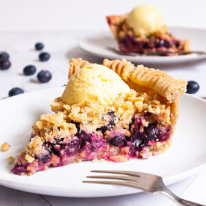 One slice of blueberry pie on a white plate with vibrant purple berries, crumble topping and a scoop of yellow ice cream. Another plate with a slice is in the background. Fresh blueberries are scattered around.