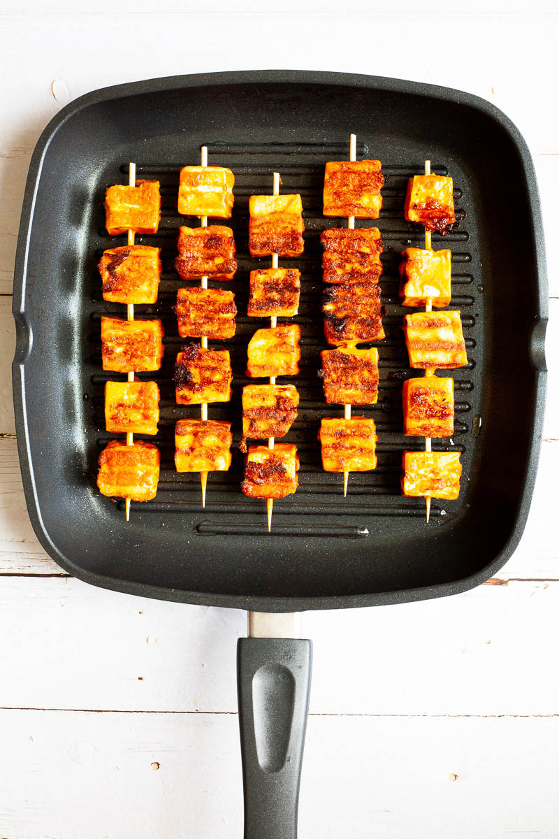 Yellow-brown tofu cubes on 5 wooden skewers are placed lengthwise in a grill pan.