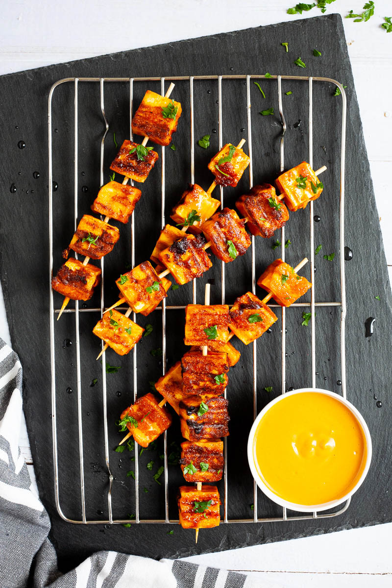 Yellow-brown tofu cubes on wooden skewers are criss cross over each other on a grilling rack placed on a black board. A small white bowl is next to them with a yellow dipping sauce.