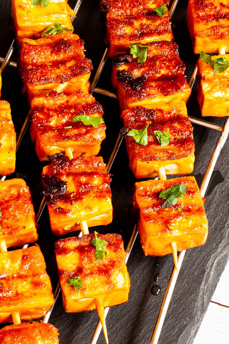 Yellow-brown tofu cubes on wooden skewers are criss cross over each other on a grilling rack placed on a black board.