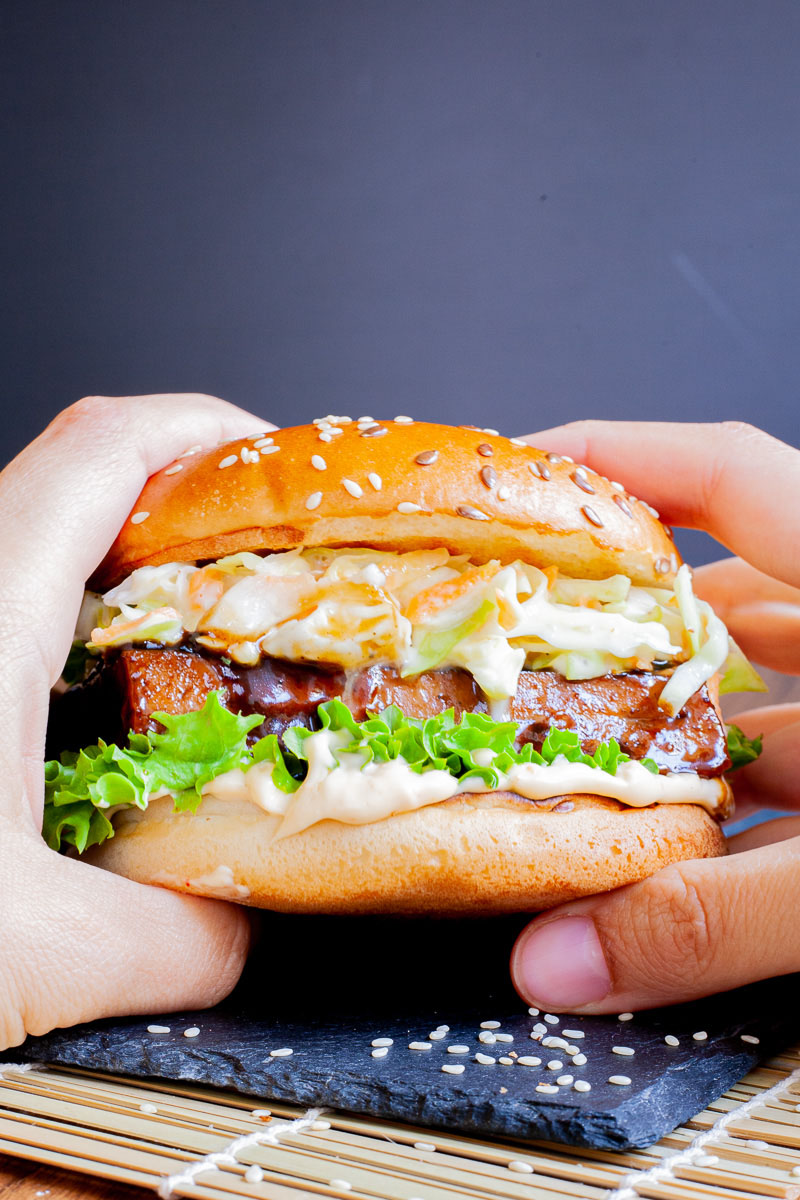 Two hands are holding a burger bun up with white sauce, green ruffled lettuce, dark glazed tofu slice, shredded cabbage and carrot in white sauce layers.
