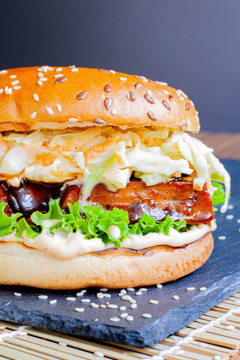 A burger bun up close with white sauce, green ruffled lettuce, dark glazed tofu slice, shredded cabbage and carrot in white sauce.