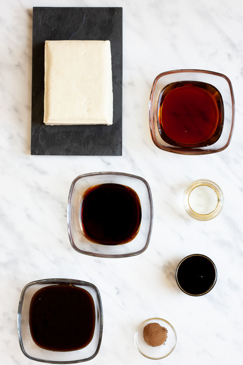 All ingredients for a tofu burger are separated into lots of glass bowls: 4 bowls with dark black sauce, one with oil and one with a brown spice. mix. And there is a block of firm tofu on a black plate
