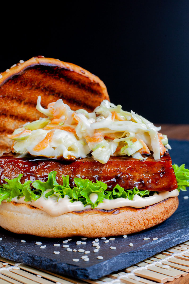 A burger bun up close with white sauce, green ruffled lettuce, dark glazed tofu slice, shredded cabbage and carrot in white sauce. The top bun is placed to the side with charcoal marks.