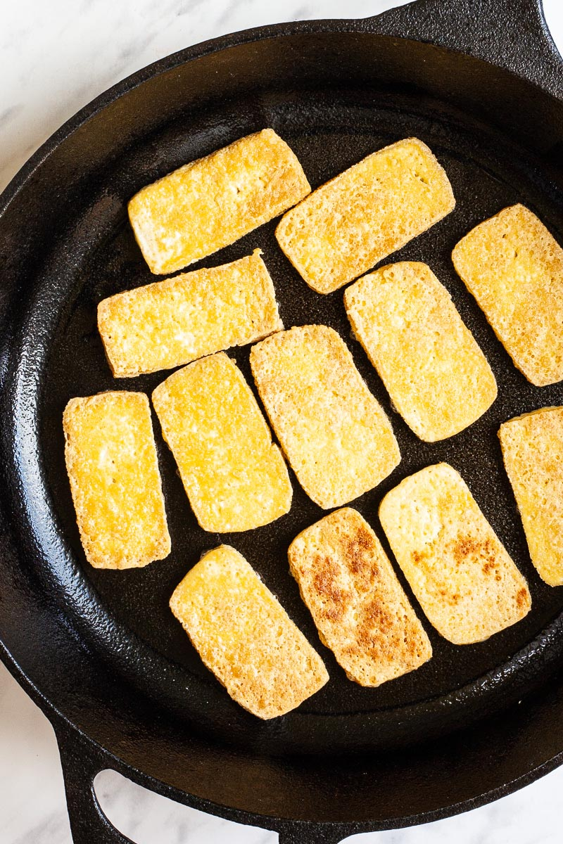 A black cast iron skillet from above with yellow tofu slices fried until golden brown and crispy