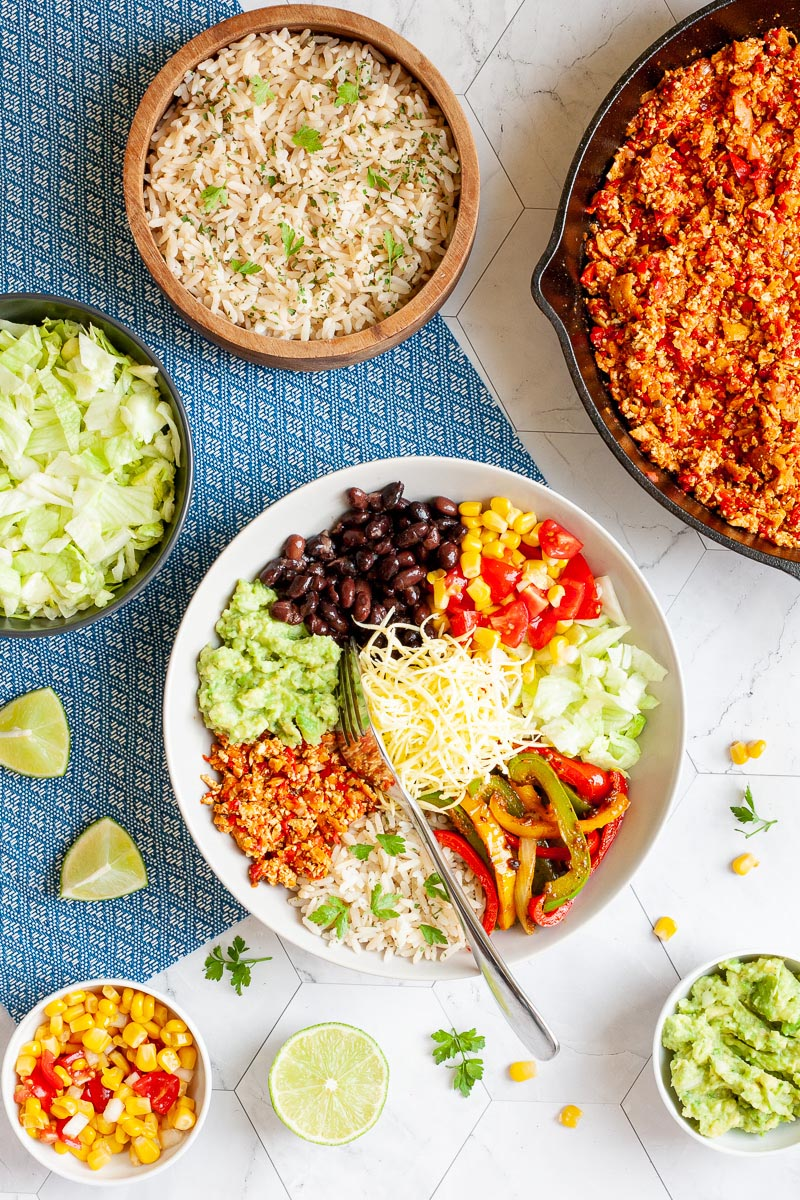 A large white plate in the middle with colorful ingredients like black beans, corn, shredded cheese, bell pepper strips, rice, shredded lettuce, avocado. Small bowls are scattered around with the same ingredients as well as a cast iron skillet with tofu crumbles in red chunky sauce