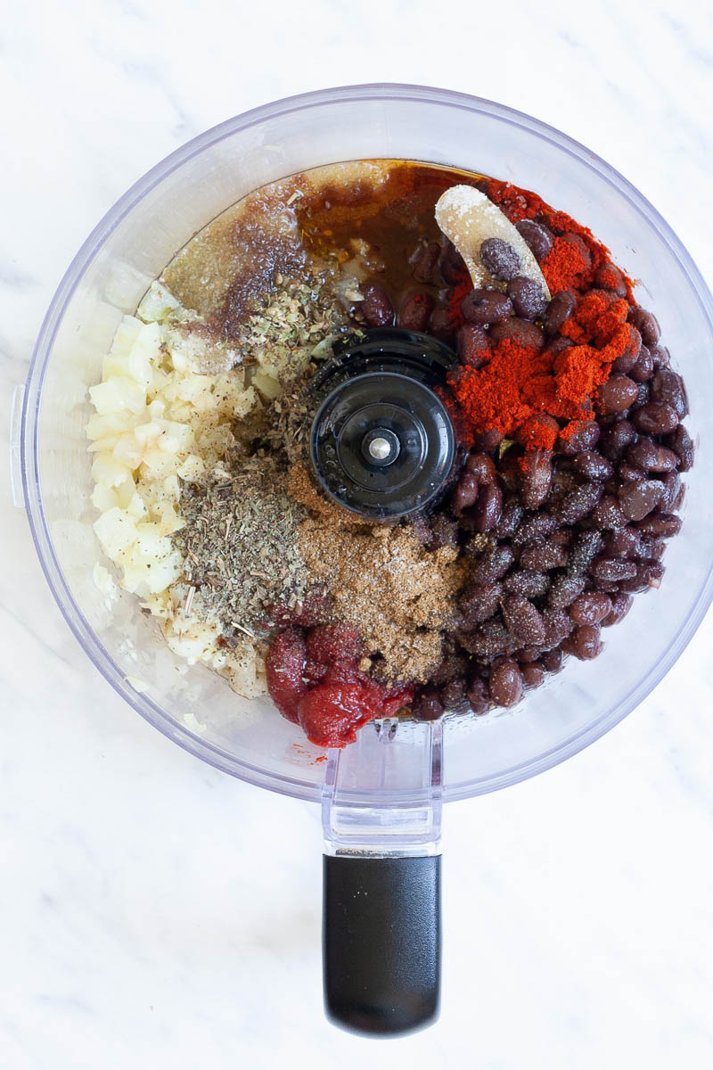 A food processor from above showing black beans, chopped onion, different colored spices