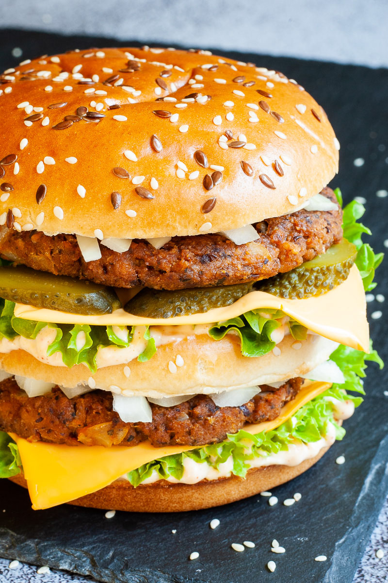A burger with layers of green ruffled lettuce, yellow sauce, thin cheese slices, dark brown burger patty twice, sliced pickles and white chopped onion.