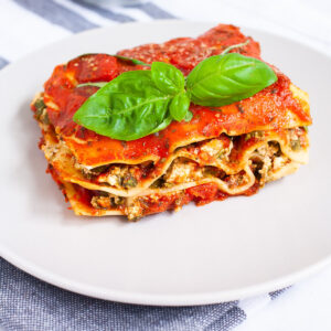 A white plate with a slice of lasagna where you can see the layers of red sauce, pasta sheets and a white ricotto and chopped spinach leaves.