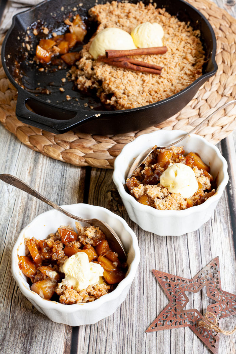 2 small white bowls with diced apples in caramel sauce, crumble topping and a scoop of yellow ice cream. A black skillet is in the background with the remaining crumbles.