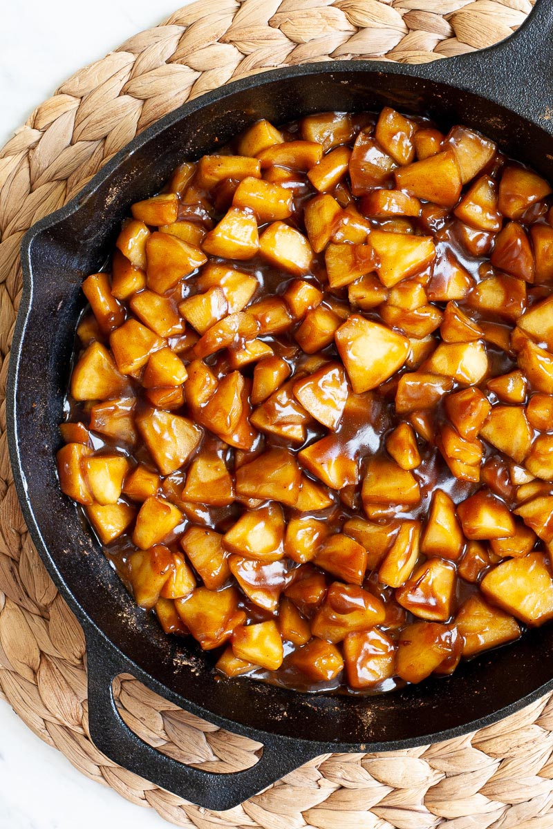 A black skillet from above with diced apples in caramel sauce.