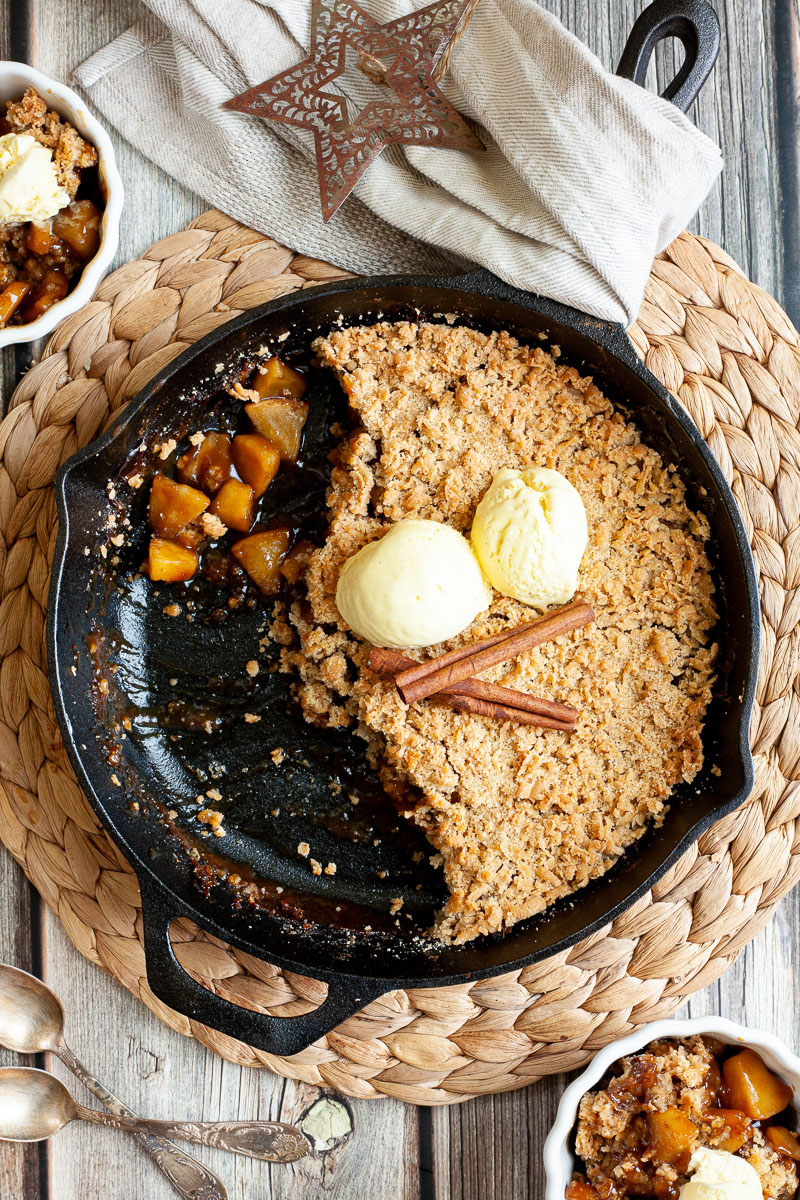 A black skillet from above with diced apples in caramel sauce, crumble topping and 2 scoops of yellow ice cream. 2 small whie bowls is filled with the apple crumble hence there is a part missing in the skillet.