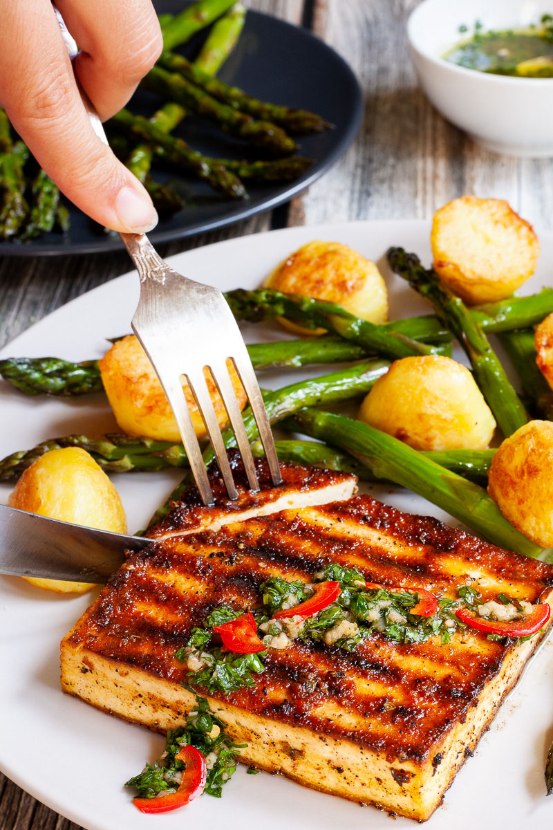 Light grey round plate with a brown, shiny tofu slice topped with a chopped green herbs served with baked half potatoes and roasted asparagus. A hand is using a fork and a knife to cut off the corner.