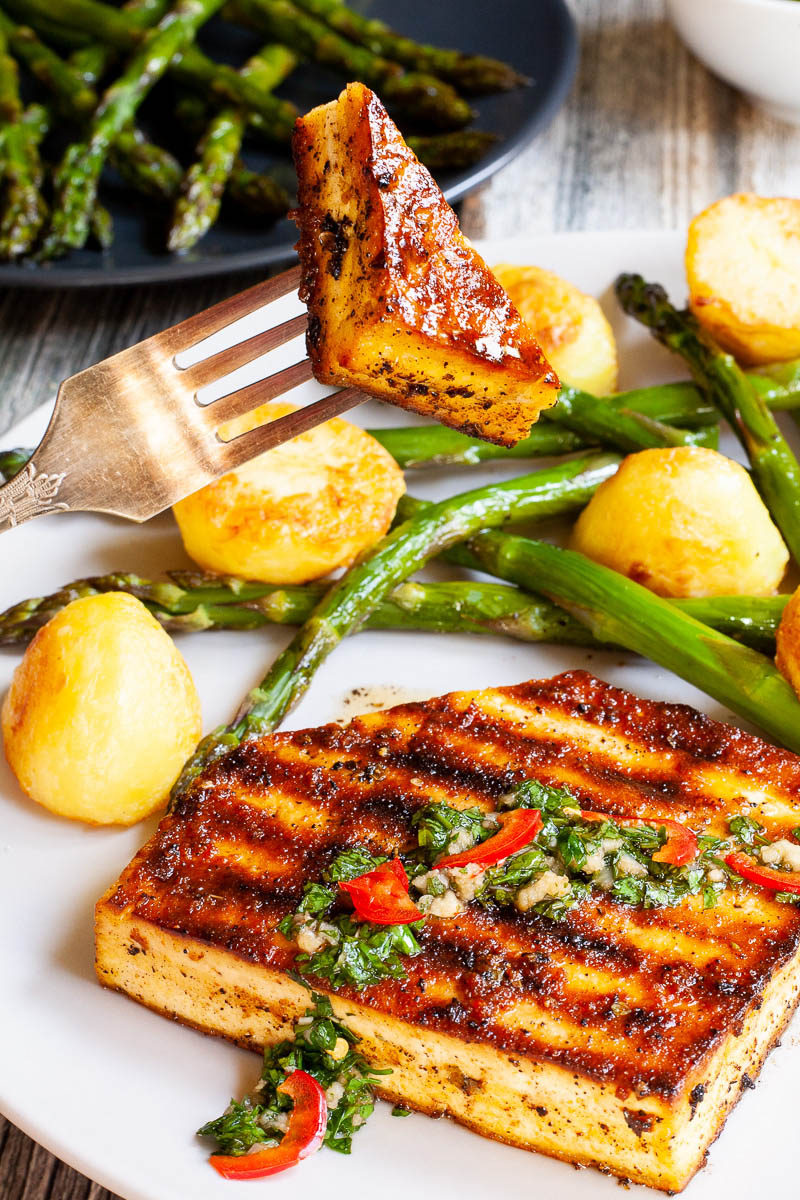 Light grey round plate with a brown, shiny tofu slice topped with a chopped green herbs served with baked half potatoes and roasted asparagus. A hand is holding a fork with one bite.