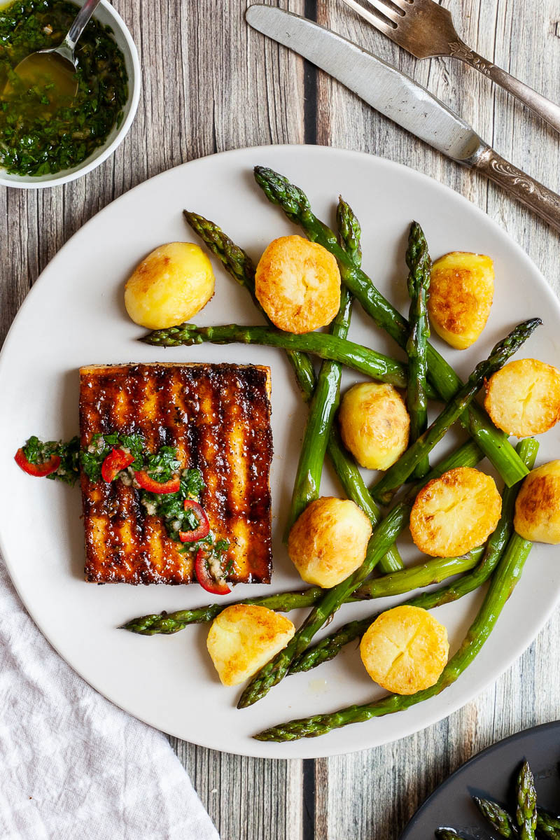 Light grey round plate with a brown, shiny tofu slice topped with a chopped green herbs served with baked half potatoes and roasted asparagus