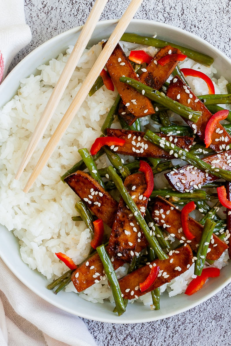 White bowl from above with white rice topped with thin dark brown tofu slices with charred edges, green beans, chopped red bell pepper and sprinkled with white sesame seeds. Light brown chopsticks are placed on the side.