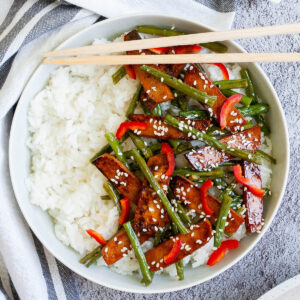 White bowl with white rice topped with thin dark brown tofu slices with charred edges, green beans, chopped red bell pepper and sprinkled with white sesame seeds.