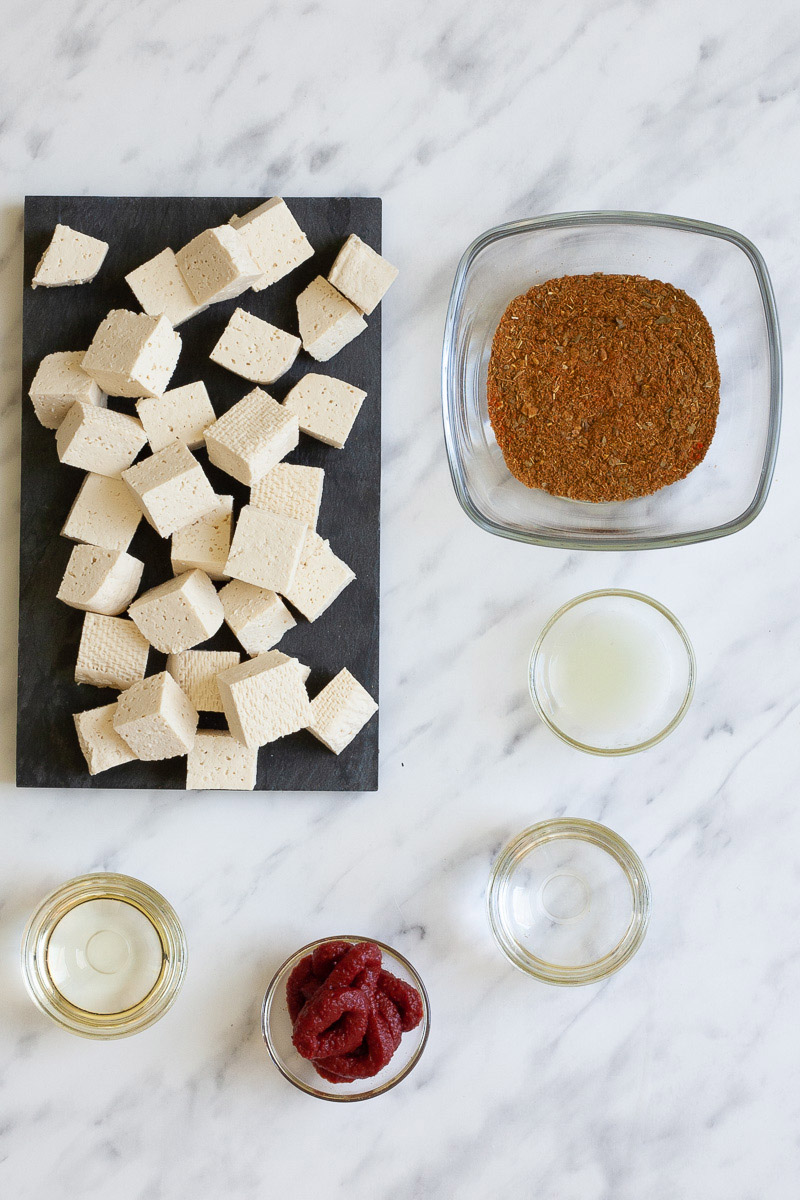 Ingredients of red curry with tofu in small glass bowls translucent liquids, red paste and red spice blend. White tofu cubes are displayed on a black plate.