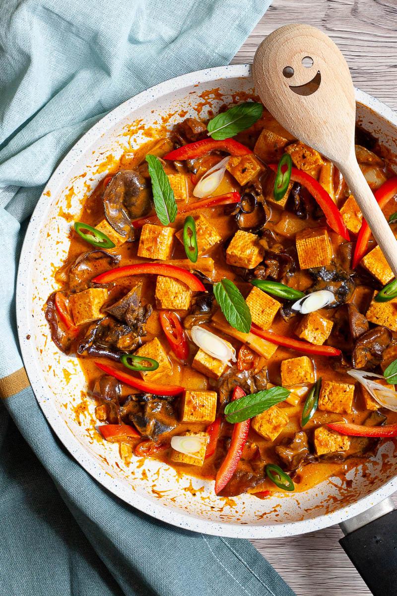 White frying pan with a darkbrown red sauce tofu cubes, sliced bell peppers, sliced green chilies, mint leaves, sliced spring onion, mushrooms slices.