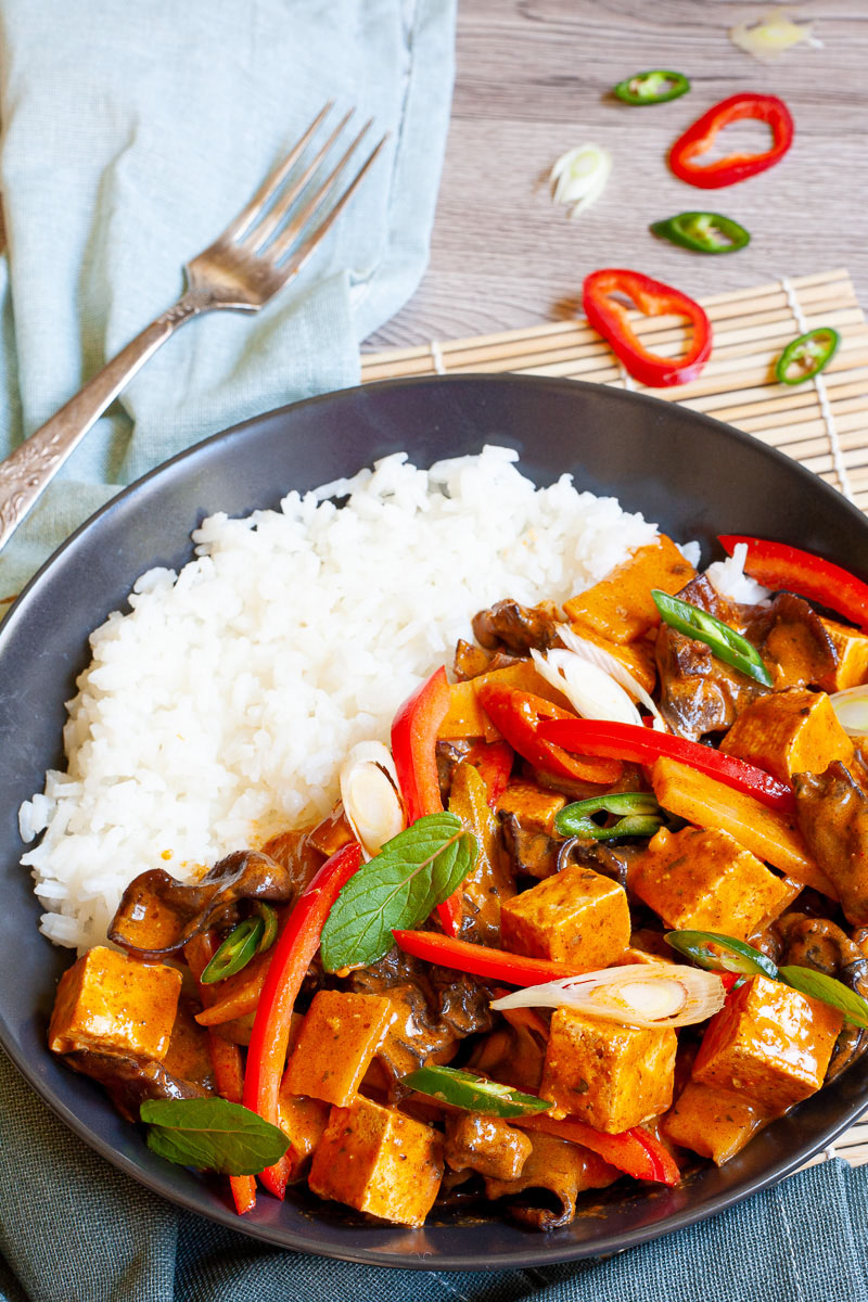 A black bowl of rice and brown red sauce with tofu cubes, sliced bell peppers, sliced green chilies, mint leaves, sliced spring onion, mushrooms slices.
