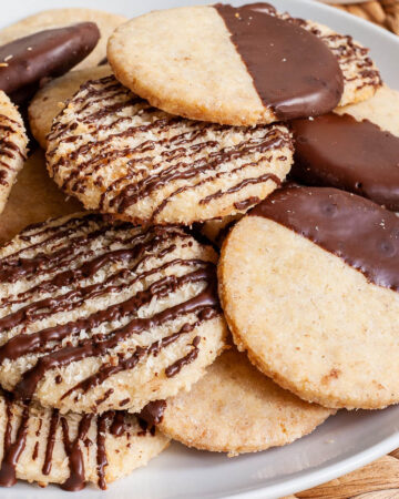 A white plate is full of thin round cookies placed on top of each other. Some cookies are partly covered in chocolate, some cookies are drizzled with chocolate so brown stripes can be seen.