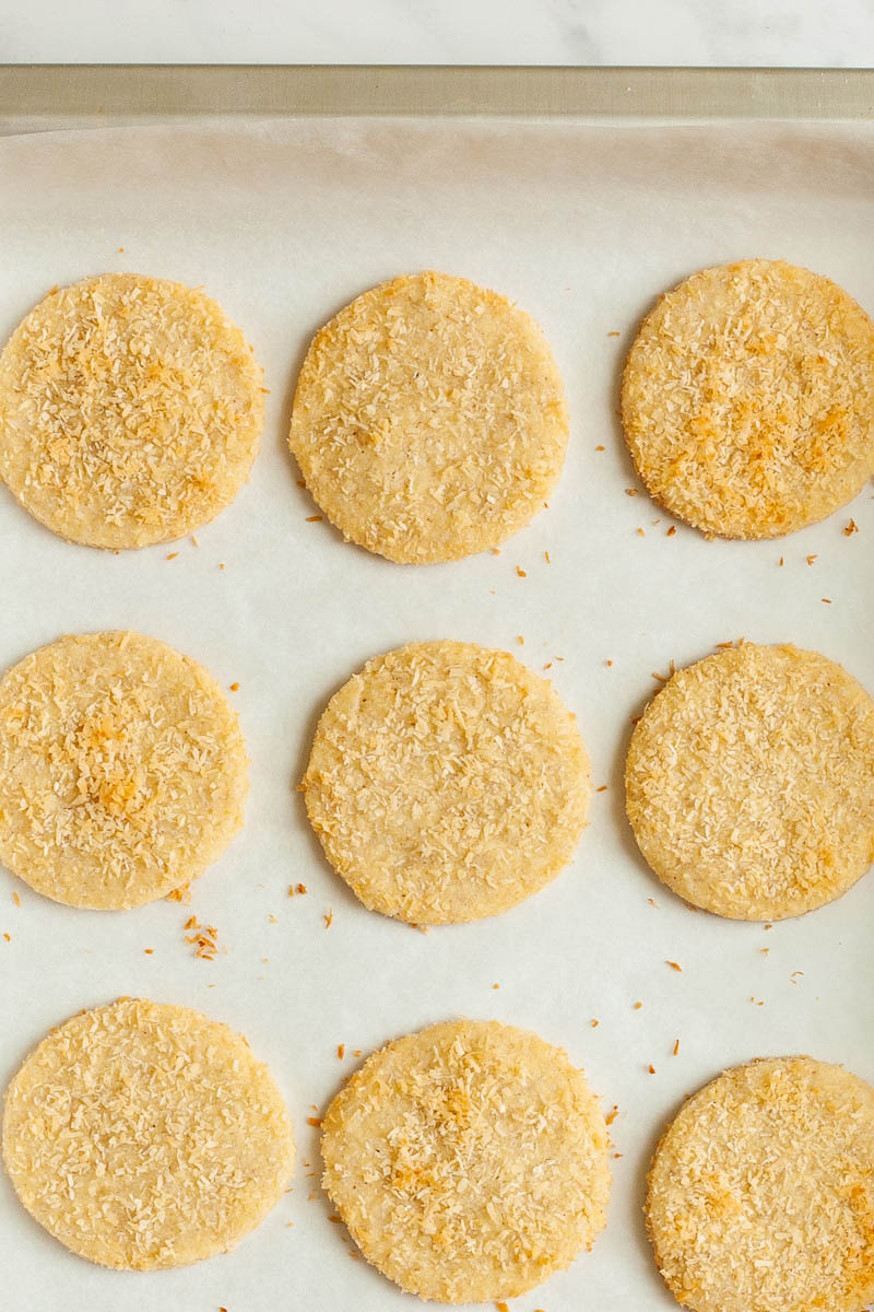 Silver baking sheet with round cookies sprinkled with shredded coconut