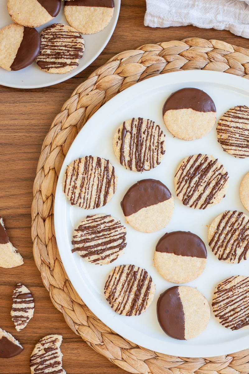 A large white plate is full of thin round cookies placed scattered but not covering each other. Some cookies are partly covered in chocolate, some cookies are drizzled with chocolate so brown stripes can be seen.