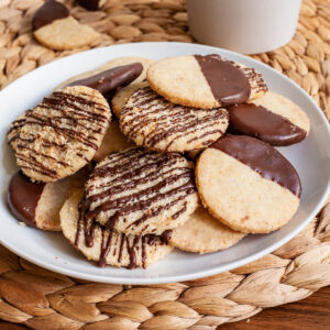 A white plate is full of thin round cookies placed placed on top of each other. Some cookies are partly covered in chocolate, some cookies are drizzled with chocolate so brown stripes can be seen.
